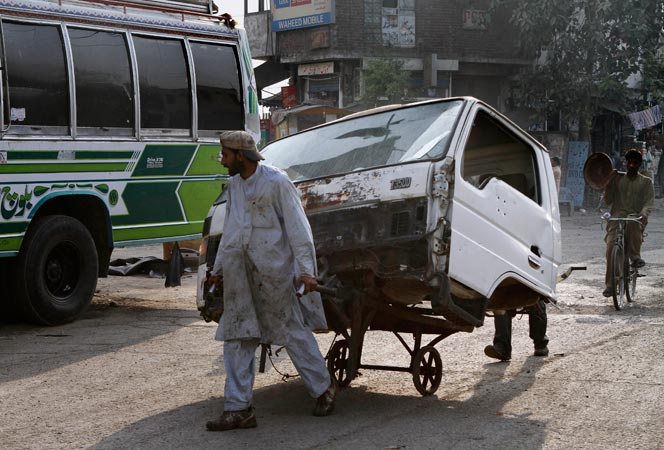 A Pakistani laborer transports the front portion of a vehicle with his handcart on a road in Lahore. – AP Photo