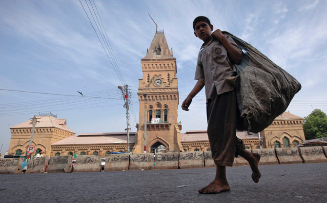 A barefooted boy carries a sack for recyclable materials as he walks past the British era Empress Market building in Karachi. The Empress Market was constructed between 1884 and 1889 and was named to commemorate Queen Victoria, Empress of India. – Reuters Photo