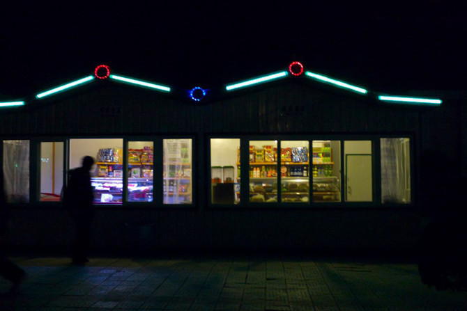 Lights from the drink and snack store beside Pyongyang railway station serves as lighting for locals to watch their steps while walking the dark. ? Photo by Elizabeth Law for Dawn.com