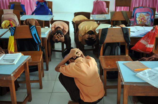 This picture taken in Banda Aceh on April 4 shows elementary school students attending an earthquake drill.  Acehnese students knew the drill by heart. When an earthquake hits, never panic and move to an open area or higher ground. So when the earth shook under their feet on April 11, teachers and students in Jeumpa Puteh senior high school coolly continued with their lessons, thinking it was the usual tremor they faced in the quake-prone Aceh province. ? Photo by AFP
