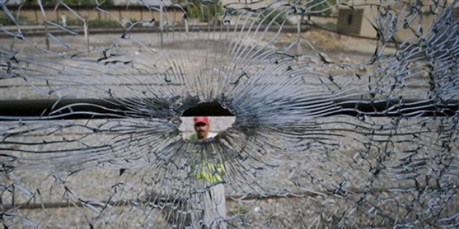 A Pakistani rescue worker is seen through the bullet-riddled window of a passenger train following an attack by unknown gunmen in Mach near Quetta, Pakistan Sunday, Aug. 28, 2011. At least five people were killed and more than a dozen others injured when a passenger train was attacked by unknown gunmen in the southwest Pakistani province of Balochistan, local media reported.