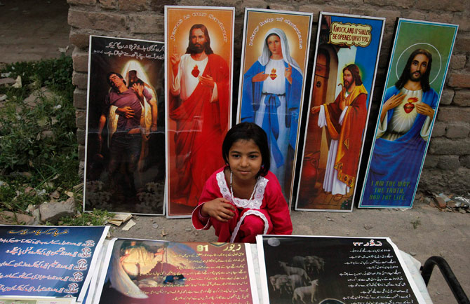 A Pakistani Christian girl sits among religious posters on display for sale in a public park during Easter celebrations in Peshawar April 8, 2012. ? Reuters Photo