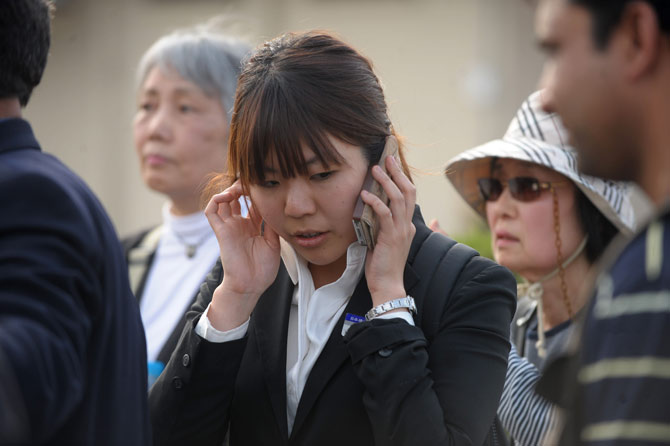 A Japanese tourist makes a call on her cellphone upon arrival at Chaklala Airbase in Rawalpindi on April 8, 2012 after evacuation by the Pakistan Air force from Gilgit.  Pakistan on April 7, evacuated 120 foreigners, mostly Japanese tourists who had been stranded in the north of the country following sectarian clashes that killed at least 14 people. ? AFP Photo