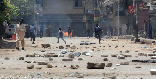 Angry protestors burnt tyres, pelted passing vehicles and police officials with stones in and around Lyari. – Photo by AFP