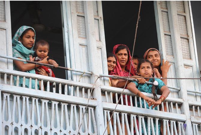 Indian women and men watch as Pakistan President Asif Ali Zardari visits the renowned 13th century shrine of Sufi saint Khwaja Moninuddin Chisti. ? AFP Photo