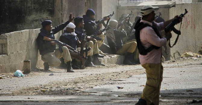 policemen-take-positions-during-a-fire-fight-with-gang-members-in-lyari