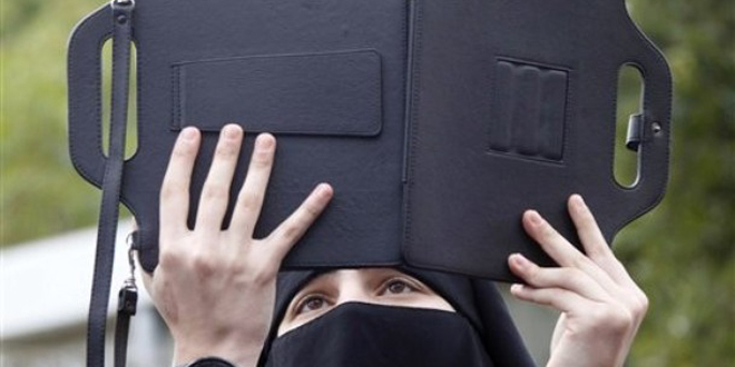 A veiled woman supporter of Islamic groups uses her iPad to film a demonstration against the Syrian regime and to show their solidarity with the Syrian people, in the southern port city of Sidon, Lebanon, on Friday Feb. 10, 2012.