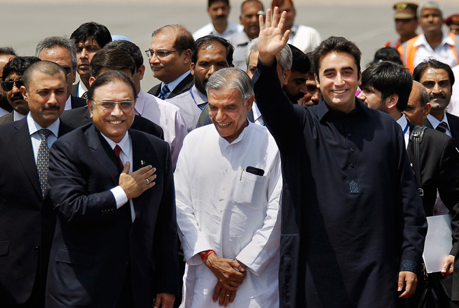 Pakistan President Asif Ali Zardari, front left, and his son Bilawal Bhutto Zardari, front right, gesture as India's Parliamentary Affairs Minister Pawan Kumar Bansal greets them after their arrival at the Palam Airfield in New Delhi, India. ? AP Photo