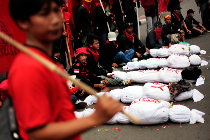 Indonesian workers display mock dead bodies representing the death of capitalism and imperialism during a rally to mark May Day in Jakarta, Indonesia, Tuesday, May 1, 2012. Thousands of Indonesian workers staged the rally demanding the government to raise minimum wage and reject outsourcing. ? Photo by AP.