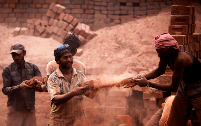 Laborers load bricks onto a truck at a brick factory on the outskirts of Jammu, India on May Day. ? Photo by AP.
