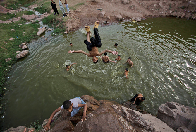 A Pakistani boy jumps from a hill in to a stream, where he and other boys swim to beat the heat, on the outskirts of Islamabad. ? Photo by AP