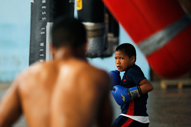 Ezequiel Quiroz, 13, known as ?Alcon?, practises with a punch bag at the Rockero Alcazar gym in the low-income neighbourhood of Curundu in Panama City. ? Photo by Reuters.