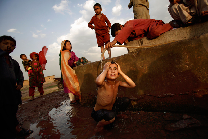 An Afghan refugee boy pours water on Doost Hamid, 7, bottom center, while bathing at a water point in a slum area on the outskirts of Islamabad. People in Pakistan are facing shortage of water due to the low level of water in the country's dams, according to Pakistani Meteorological Department. ? Photo by AP