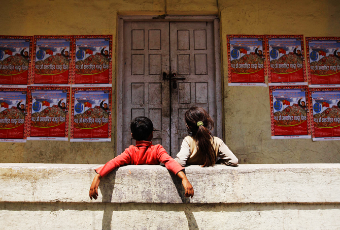 Children look at Labour Day posters during an event commemorating Labour Day in Kathmandu. ? Photo by Reuters.