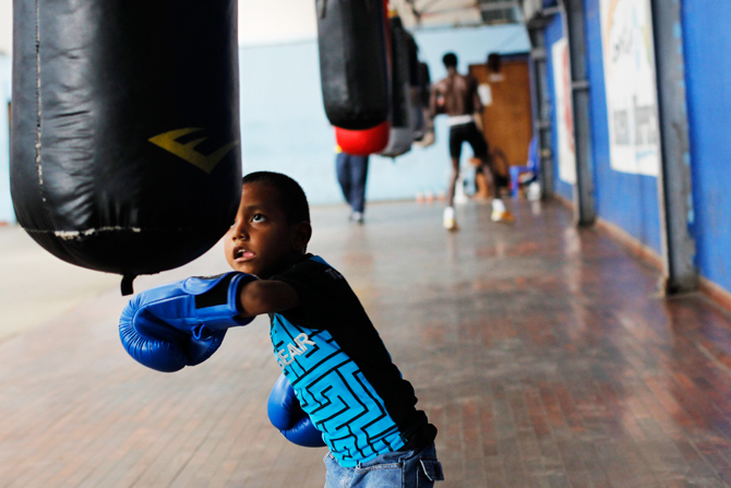 A boy practices with a punch bag at the Rockero Alcazar gym in the low-income neighbourhood of Curundu in Panama City. ? Photo by Reuters.