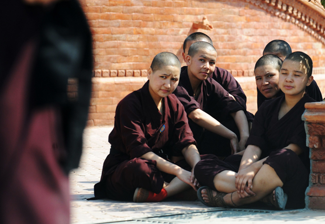 Buddhist nuns watch other nuns practising Kung-fu  at the Amitabha Drukpa Nunnery on the outskirts of Kathmandu. ? Photo by AFP.