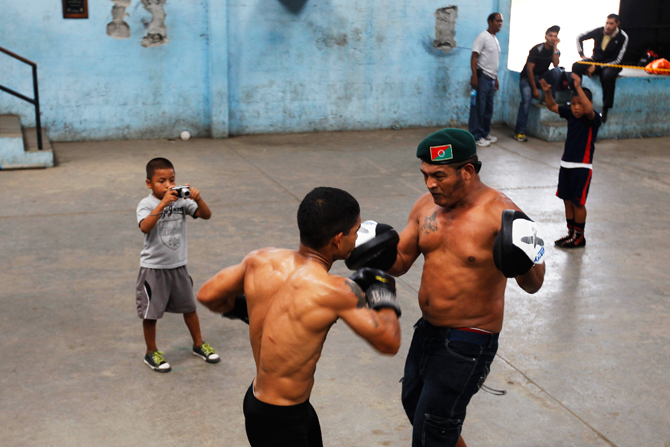 A boy takes photographs of boxers sparring during a training session at the Rockero Alcazar gym in the low-income neighbourhood of Curundu in Panama City. ? Photo by Reuters.