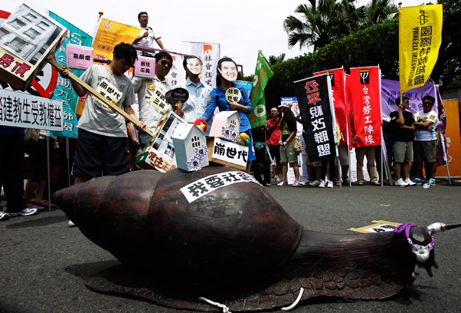 "Activists stand near a snail statue, with a sticker reading ""I want social housing"", as they take part in a May Day rally in Taipei. Hundreds of people took to the streets on Tuesday in the annual May Day (Labour Day) parade to demand more labour rights and higher pay. ? Photo by Reuters."