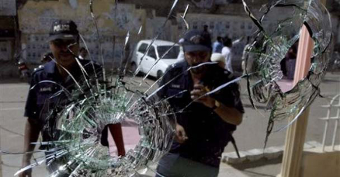 Policemen seen through bullet-riddled wind shield of a car in Karachi.—File Photo