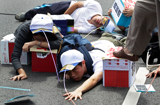 "Protesters act out a skit during a May Day rally in Taipei. Hundreds of people took to the streets on Tuesday in the annual May Day (Labour Day) parade to demand more labour rights and higher pay. The Chinese characters on the blue box read, ""High housing price"". ? Photo by Reuters."