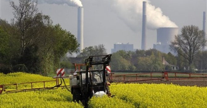 A farmer fertilizes rapeseed plants.—AP Photo