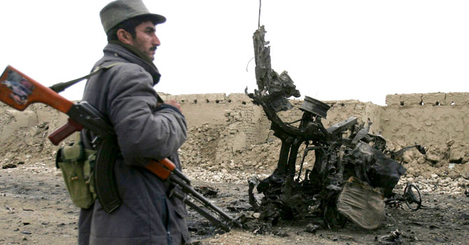 An Afghan policeman stands at the site of a roadside bomb attack. – File photo by AP