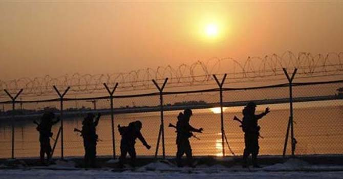 "South Korean army soldiers check barbed-wire fence in Hwaseong, South Korea, before sunset Thursday, Dec. 29, 2011. North Korea declared Kim Jong Il's son and successor ""supreme leader"" of the ruling party, military and the people during a memorial Thursday for his father in the government's first public endorsement of his leadership. (AP Photo/Yonhap)  Korea Out"