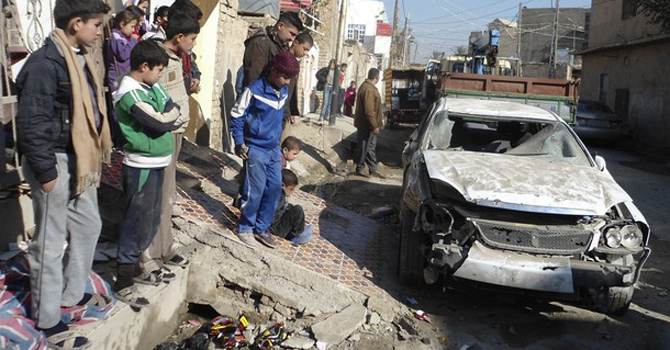 Boys look at a vehicle damaged by a bomb attack in Baquba.—Reuters Photo