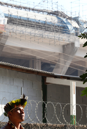 A Brazilian native Indian stands inside the former Indian Museum, in front of renovation works for Maracana stadium in Rio de Janeiro.