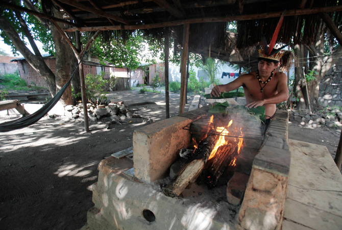 Brazilian native Indian Afonso Chamacari cooks a fish inside the former Indian Museum in Rio de Janeiro.