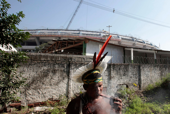 A Brazilian native Indian smokes inside the former Indian Museum in front of renovation works for Maracana stadium in Rio de Janeiro.