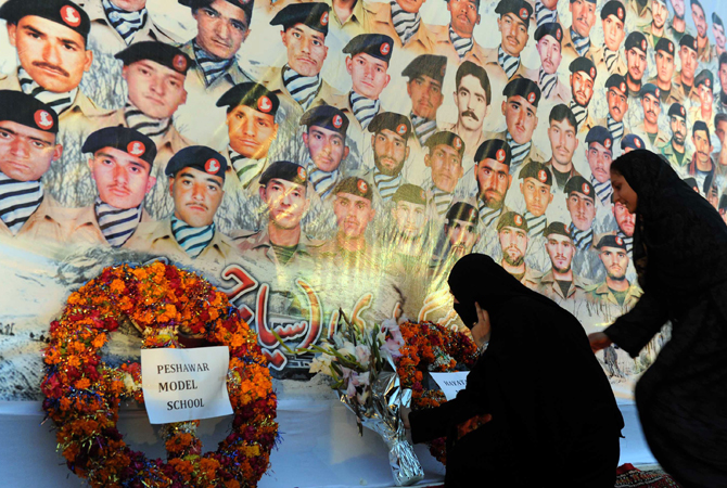 Veiled women place flowers underneath the portraits of Pakistani soldiers victims of an avalanche, during a ceremony in Peshawar. ? Photo by AFP