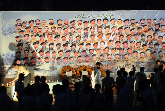 People gather in front of the portraits of Pakistani soldiers victims of an avalanche, during a ceremony in Peshawar. ? Photo by AFP