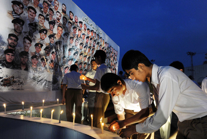 Young men place candles in front of the portraits of Pakistani soldiers victims of an avalanche, during a ceremony in Peshawar. ? Photo by AFP