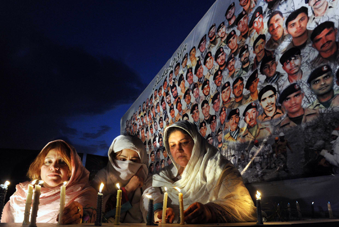 Women place candles in front of the portraits of Pakistani soldier's victims of an avalanche, during a ceremony in Peshawar. ? Photo by AFP