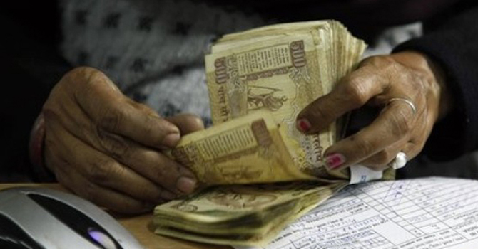 Cashier counts Indian rupees.—File Photo