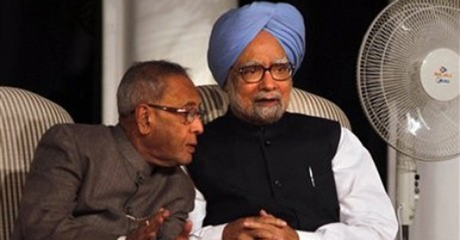 Indian Prime Minister Manmohan Singh, blue-turban, listens to Finance Minister Pranab Mukherjee.—File Photo