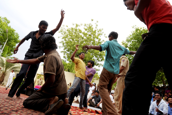 Inmates dance in front of other prisoners to music being performed on a nearby stage during a small concert at the Tihar jail in New Delhi on April 26, 2012.