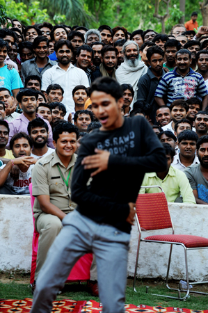 An inmate dances in front of other prisoners to music being performed on a nearby stage during a small concert at the Tihar jail in New Delhi on April 26, 2012.