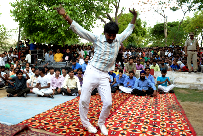 An inmate dances in front of other prisoners to music being performed on a nearby stage during a small concert at the Tihar jail in New Delhi on April 26, 2012
