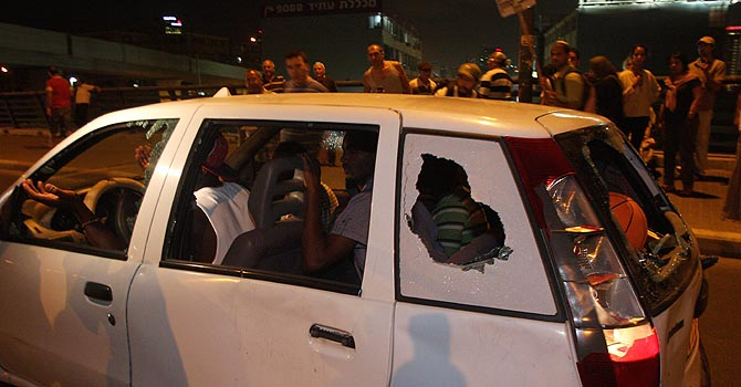 African immigrants drive a car whose windows were shattered by Israeli protesters taking part in a rally against the government's handling of the flow of African migrants into Israel, in Tel Aviv on May 23, 2012. AFP PHOTO/RONI SCHUTZER == ISRAEL OUT ==