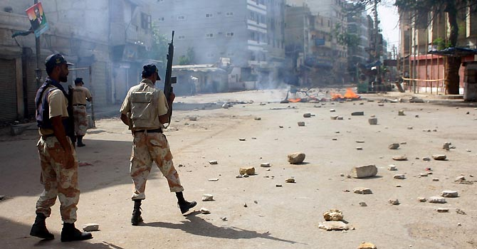 Paramilitary rangers stand while Angry protestors burnt tyres on the road in Lyari during a demonstration on the call of strike by Awami Tahreek and JSQM. At least two people have been killed in parts of Karachi in firing incidents as Sindhi nationalists observe strike against the killing of Jiye Sindh Mutahida Mahaz (JSMM) leader and firing at a political rally. in Karachi on Wednesday, May 23, 2012. (Rizwan Ali/PPI Images).
