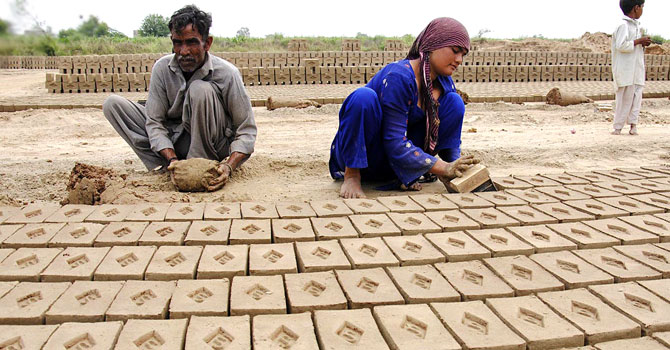 Labourers work at a brick kiln near Lahore.
