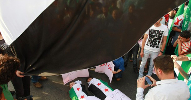 Syrian refugees carry a giant Syrian opposition flag as they surround children lying covered with Syrian opposition flags, during a protest.—Reuters Photo