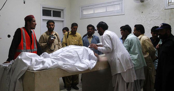 People gather near the body of Chief Jail Warden who was killed in firing by unknown assailants. ONLINE PHOTO by Ahmad Kakar