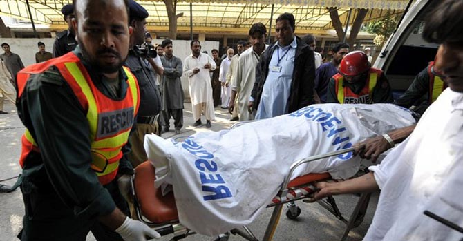 Pakistani rescue workers move a body at
