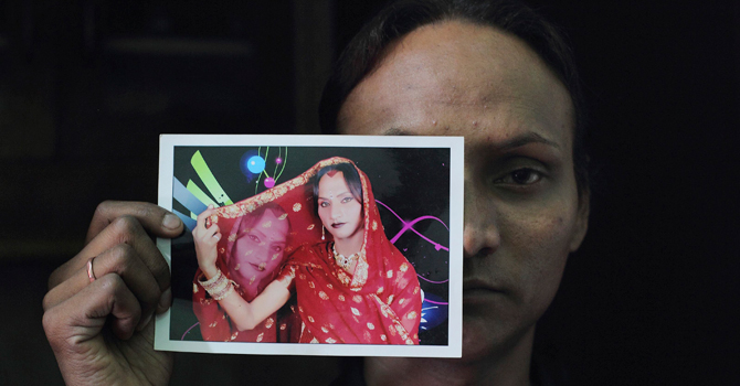 Seema, 33, displays his picture in which he's dressed as a woman at his residence in New Delhi.—Reuters Photo