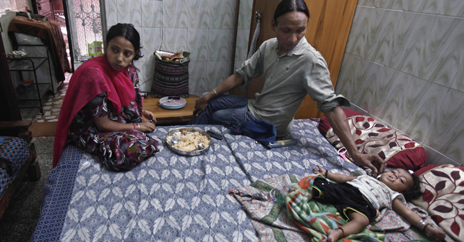 Seema (C) 33, feeds his daughter as his wife eats her lunch at their residence in New Delhi.—Reuters Photo