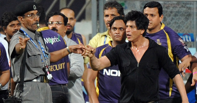 Shah Rukh Khan gestures towards a security guard blowing a whistle to direct children accompanying him off the playing field after the IPL Twenty20 cricket match between Mumbai Indians and Kolkata Knight Riders at The Wankhede Stadium in Mumbai.—AFP Photo