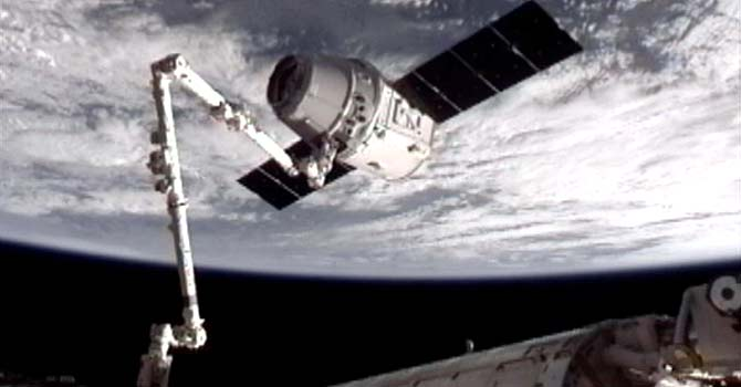 image provided by NASA-TV shows the SpaceX Dragon commercial cargo craft, top, after Dragon was grappled by the Canadarm2 robotic arm and connected to the International Space Station. – Photo by AP